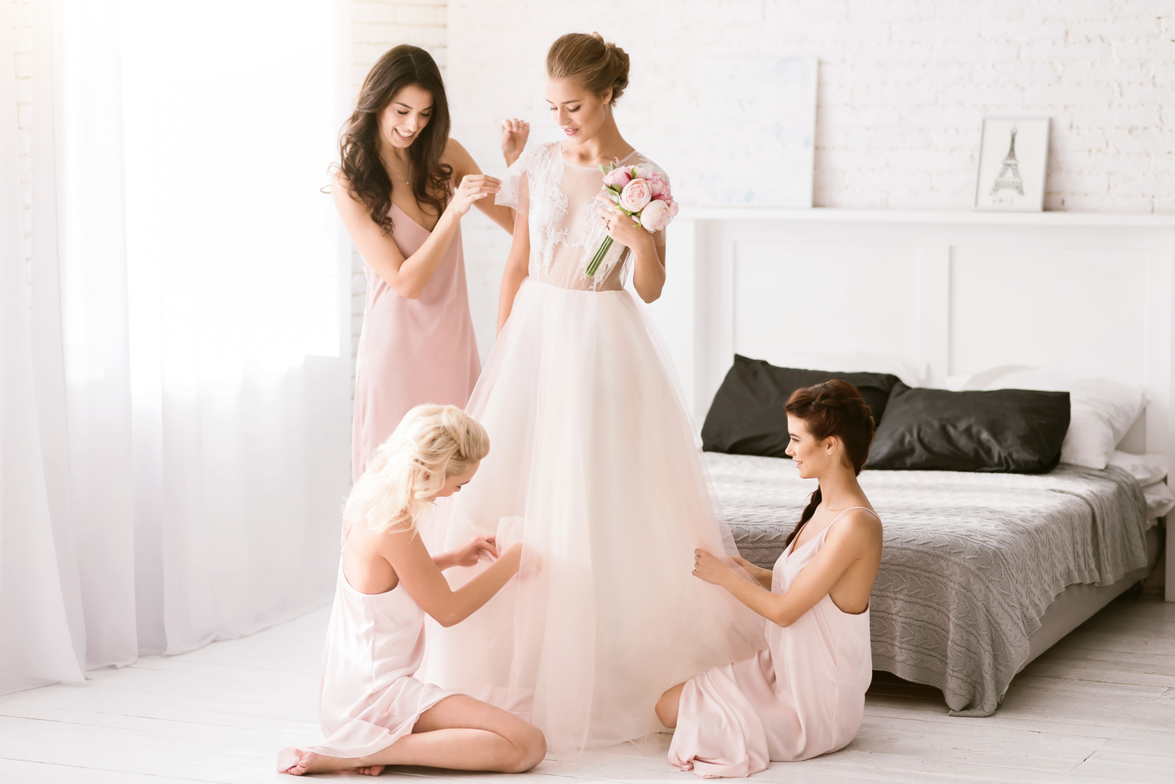 Delighted bridesmaids helping the bride to get ready